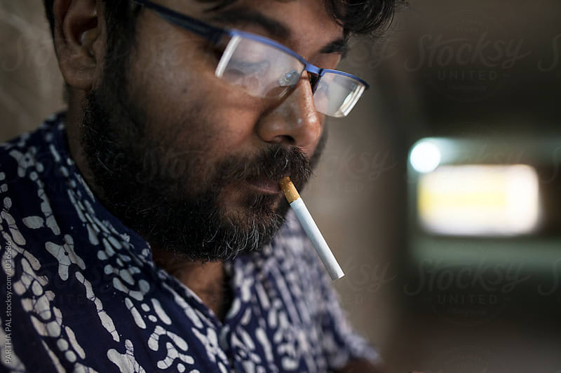 A man smoking Cigarette  by PARTHA PAL for Stocksy United