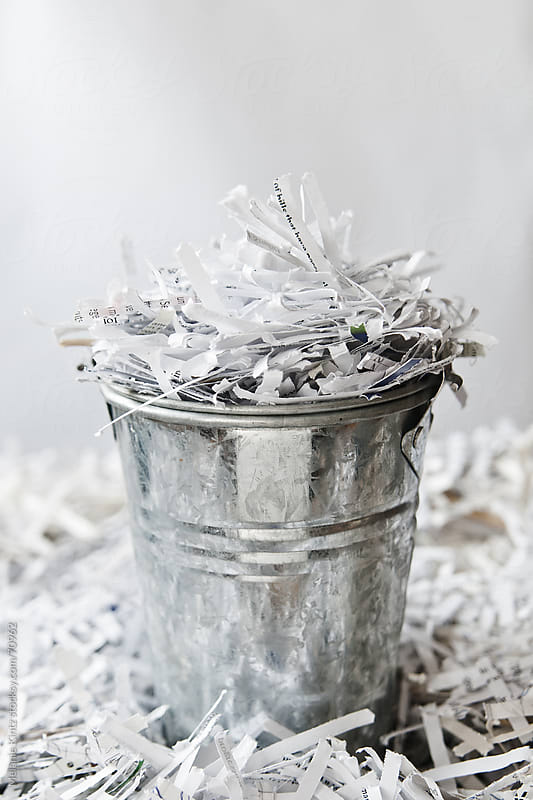 bucket full of  shredded paper pieces  by Melanie Kintz for Stocksy United