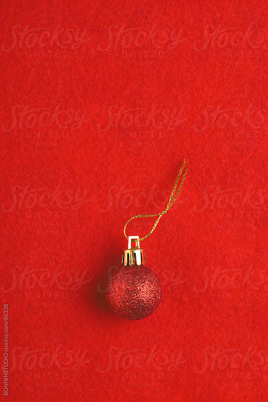 Red christmas ball over red background. Overhead photo. by BONNINSTUDIO for Stocksy United