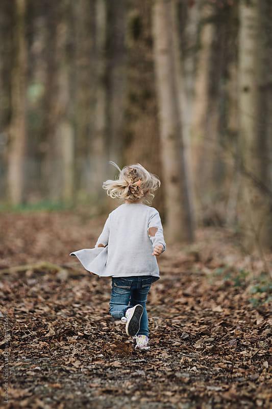 cute blond little girl running through autumnal forest by Leander Nardin for Stocksy United