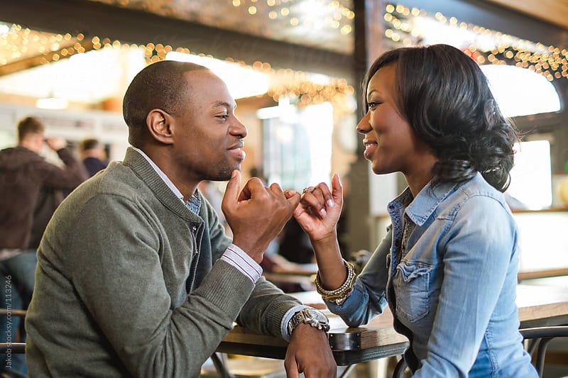 A beautiful african-american couple in love pinky promising in a restaurant by Jakob for Stocksy United