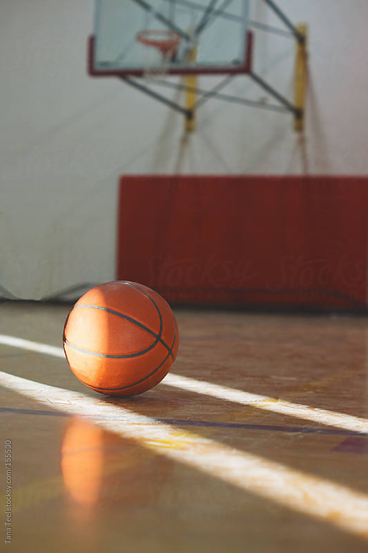 A basketball sits between sunbeams on a basketball court by Tana Teel for Stocksy United