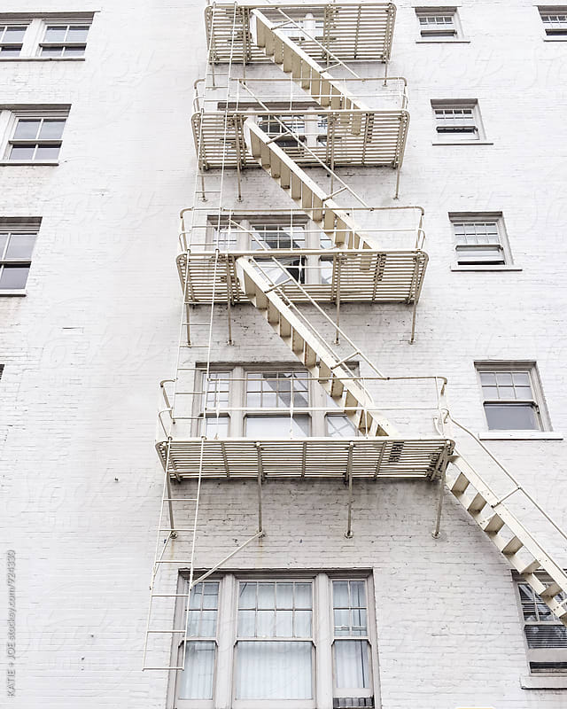 White brick apartment fire escape stairs by KATIE + JOE for Stocksy United