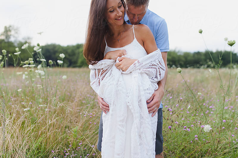 A husband kisses his pregnant wife's shoulder by Amanda Worrall for Stocksy United