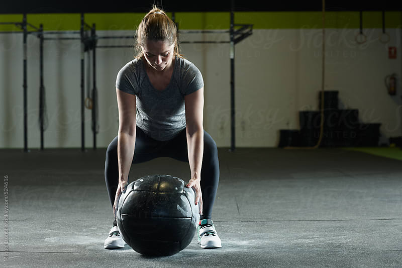 Fit woman getting ready to lift a heavy training ball by Miquel Llonch for Stocksy United
