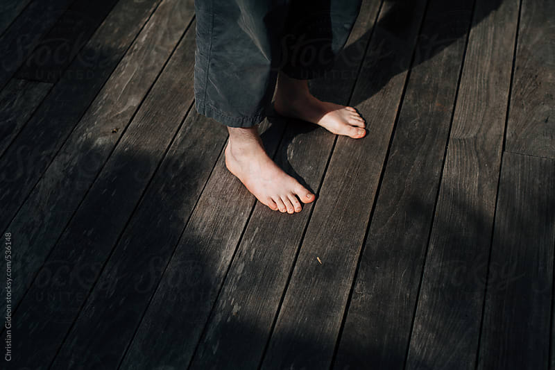 Bare feet on wood by Christian Gideon for Stocksy United
