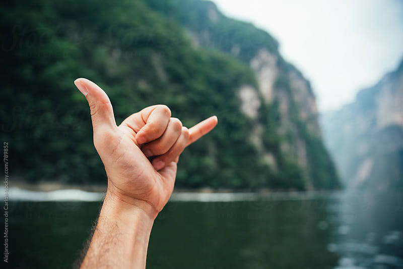Close up of a male hand making a cool sign with fingers with a scenic view of the canyon and lake in Chiapas, Mexico. POV view by Alejandro Moreno de Carlos for Stocksy United