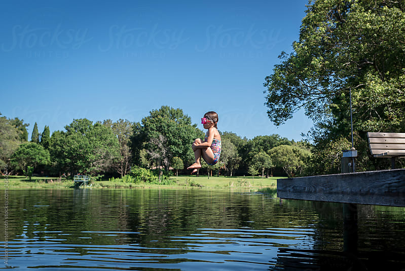 Girl Doing Cannonball Trick Off Dock by Alison Winterroth for Stocksy United