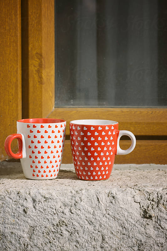 two coffee/ tea cups on a window by B & J for Stocksy United