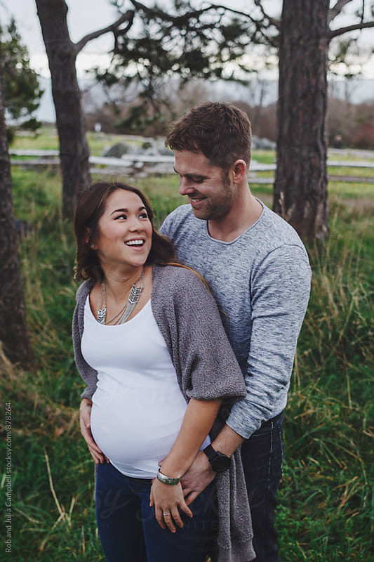 Happy young pregnant couple laughing together outside in nature by Rob and Julia Campbell for Stocksy United