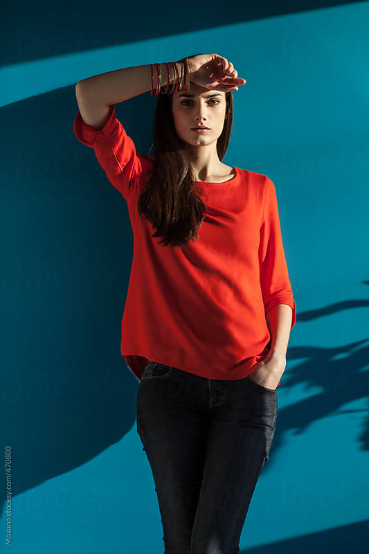 Young Woman in a Red Top Standing Against Blue Wall by Mosuno for Stocksy United