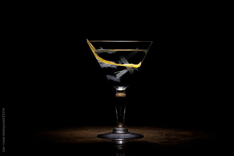 Transparent cocktail with lemon peel by Lior + Lone for Stocksy United
