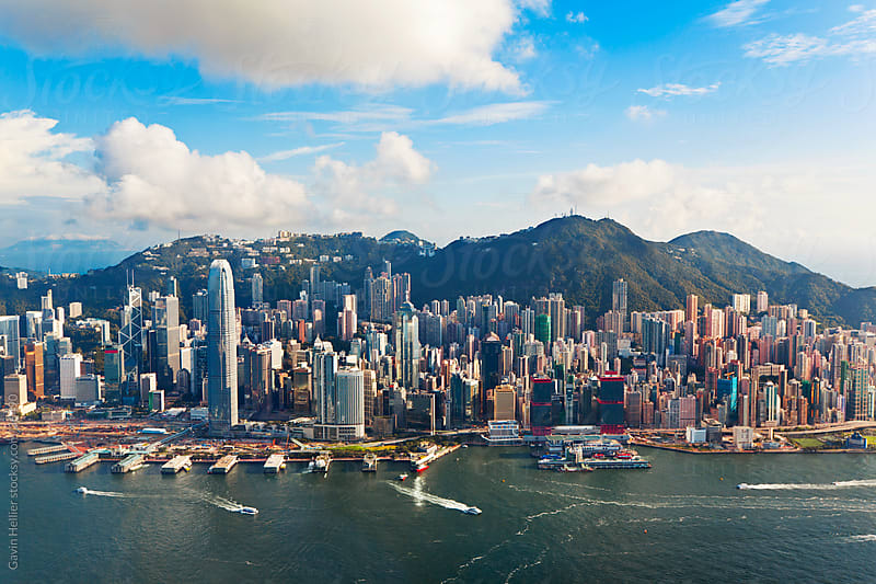 Elevated view across the busy Hong Kong harbour,  Central district of Hong Kong Island and Victoria Peak, Hong Kong, China by Gavin Hellier for Stocksy United