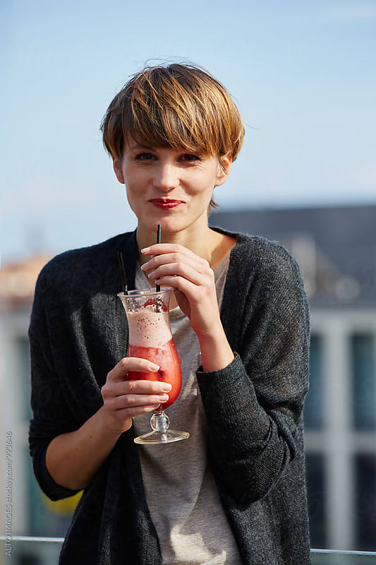 Happy Woman Drinking Cocktail On Hotel Terrace by ALTO IMAGES for Stocksy United