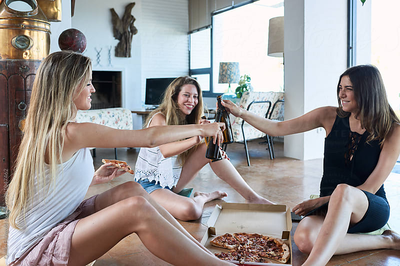 Friends toasting with beer and pizza at home by Guille Faingold for Stocksy United