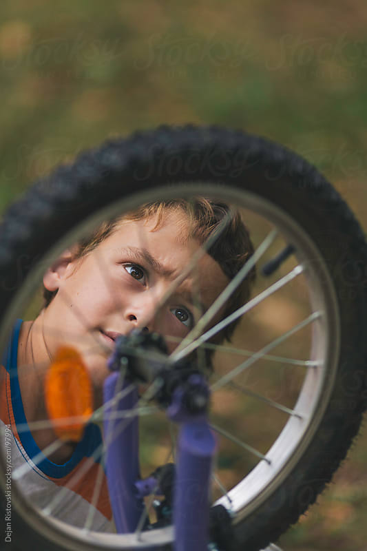 Child face looking at  the bicycle wheel by Dejan Ristovski for Stocksy United
