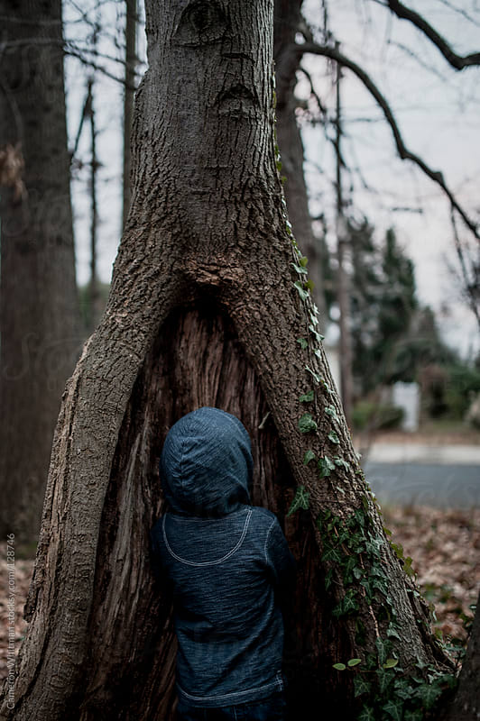 Peek A Boo, Boy hiding inside the base of a tree  by Cameron Whitman for Stocksy United