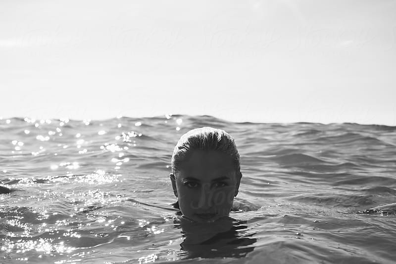 Young woman relaxing in the sea by Simone Becchetti for Stocksy United