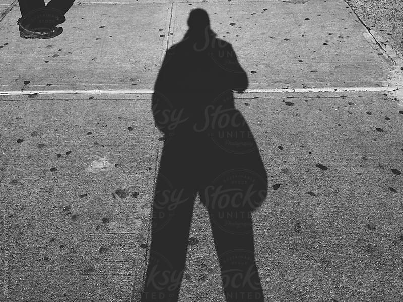Shadows and silhouette of a man and woman walking the sidewalks of an urban city by Greg Schmigel for Stocksy United