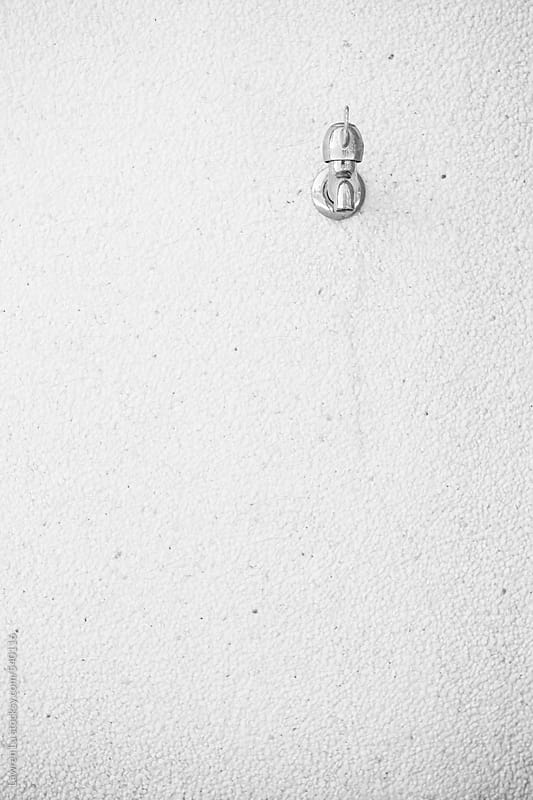 Iron faucet on white cement wall by Lawren Lu for Stocksy United