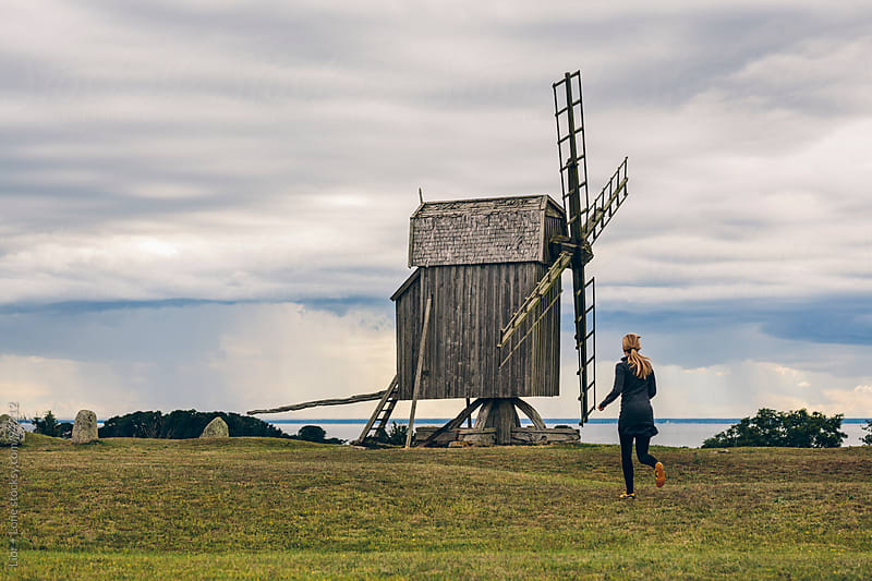 Woman running in a field towards windmill  by Lior + Lone for Stocksy United