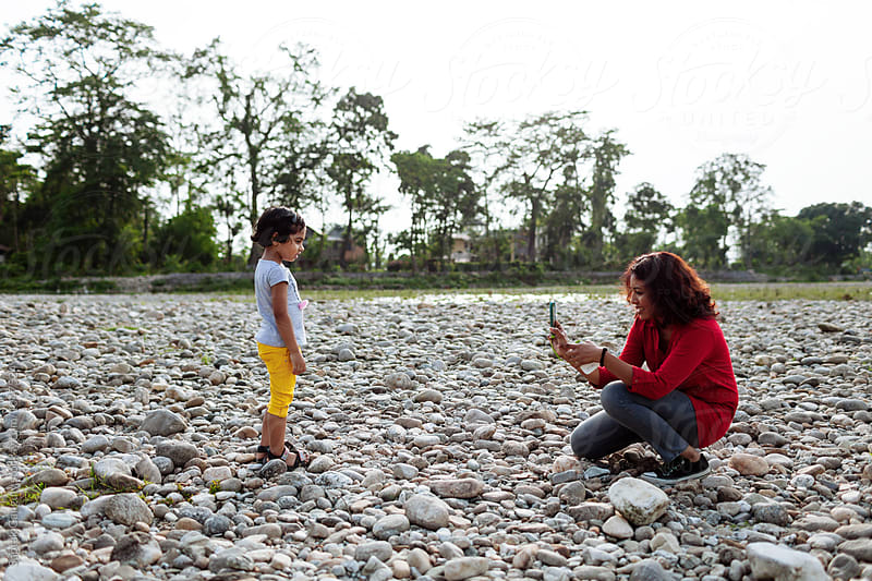 Woman taking photo of a child with mobile phone by Saptak Ganguly for Stocksy United