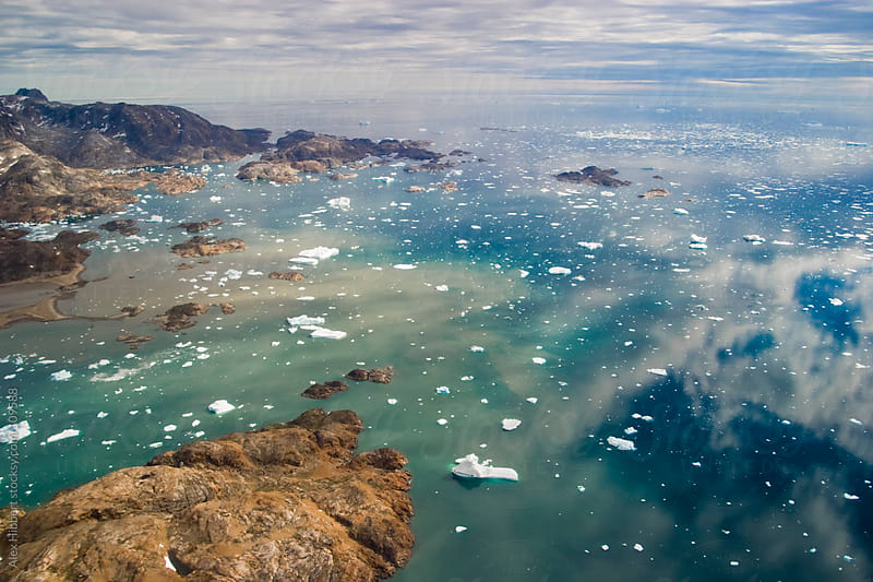 Aerial view of the Greenlandic mountains and water near Kulusuk, by Alex Hibbert for Stocksy United