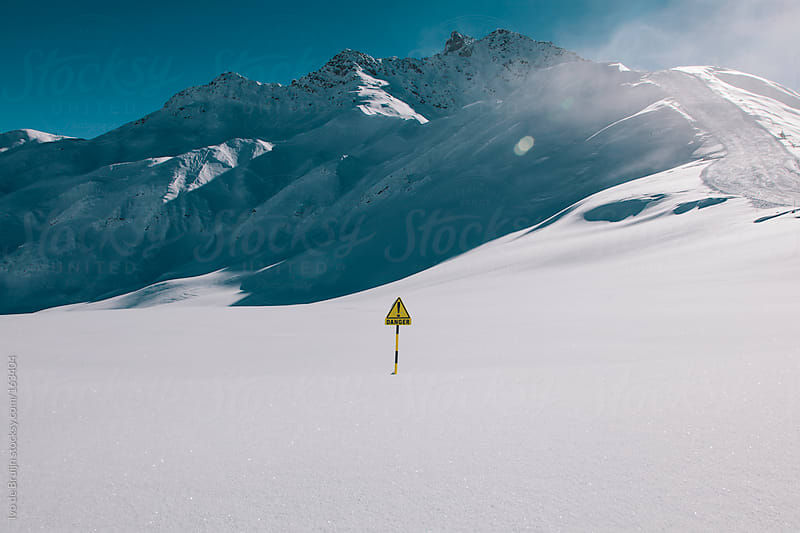 Danger sign in the middle of field of snow surrounded by mountains by Ivo de Bruijn for Stocksy United