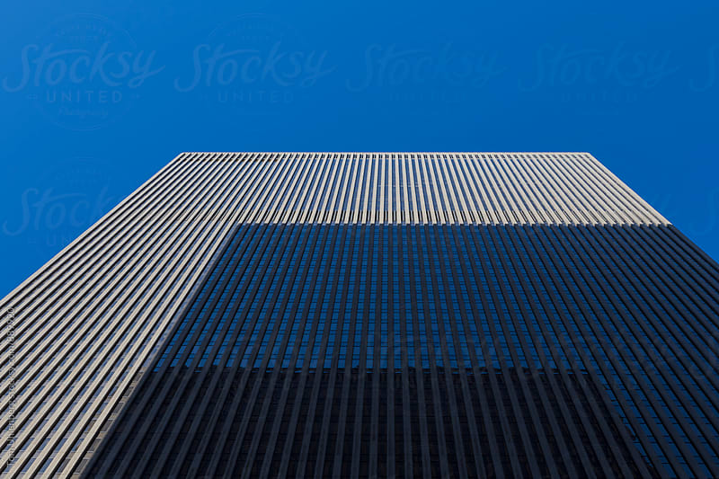 Upward Perspective of a Skyscraper Shadowed by Another Skyscraper by Tom Uhlenberg for Stocksy United
