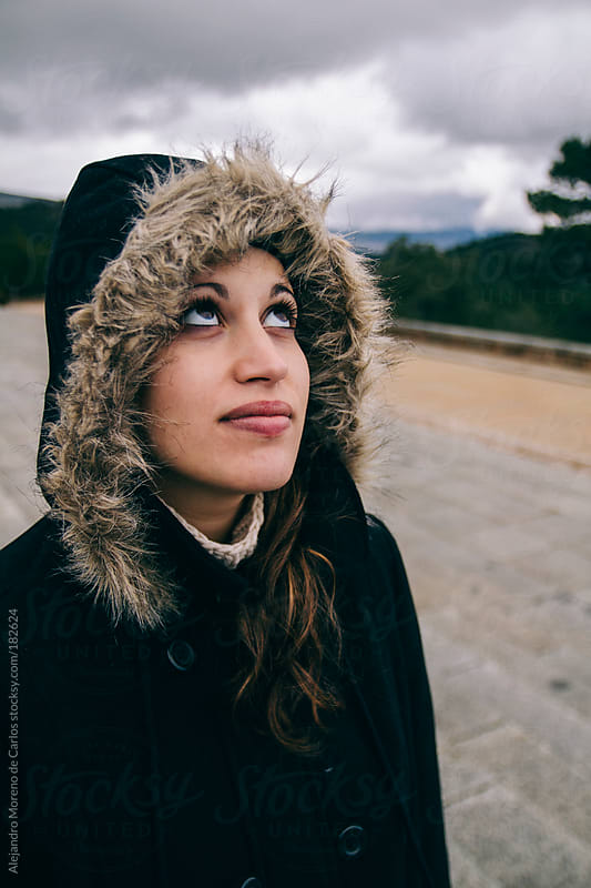 Young woman wearing parka coat and hood looking up to the sky by Alejandro Moreno de Carlos for Stocksy United