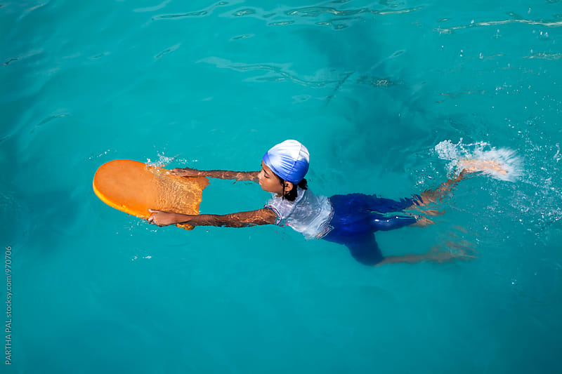 A girl learning swimming in a pool by PARTHA PAL for Stocksy United