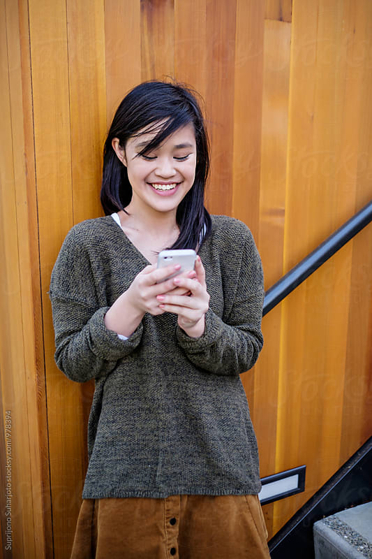Asian college student texting on her phone on campus by Suprijono Suharjoto for Stocksy United