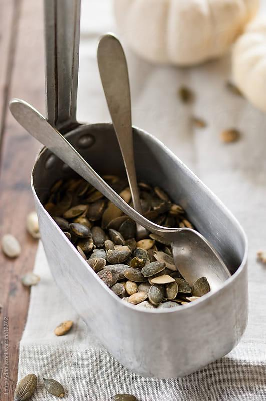 alluminum pot full of pumpkin seeds by Laura Adani for Stocksy United