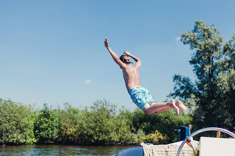 Boy in swim shorts jumping from a boat into the lake  by Cindy Prins for Stocksy United