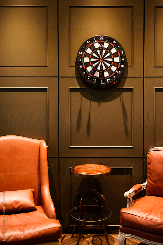 Darts on wall with two orange leather arm chairs by Lawren Lu for Stocksy United