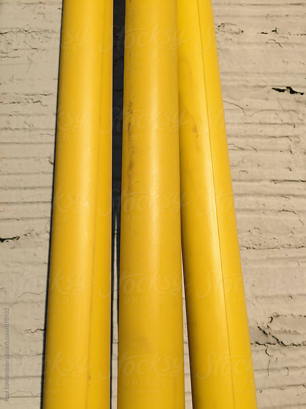 Yellow plastic tubing covering utility cables, close up by Paul Edmondson for Stocksy United