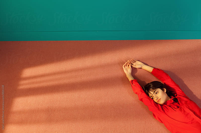 woman lying  down on the floor of a room by Ulaş and Merve for Stocksy United