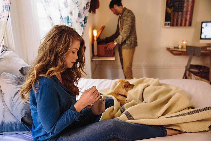 Young couple relaxing in bedroom with dog by Trinette Reed for Stocksy United