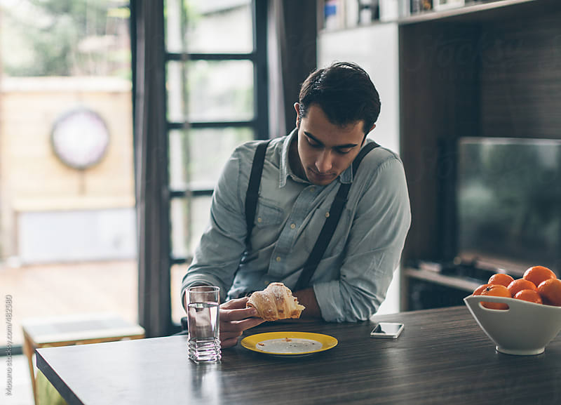 Handsome Man Eating Breakfast  by Mosuno for Stocksy United