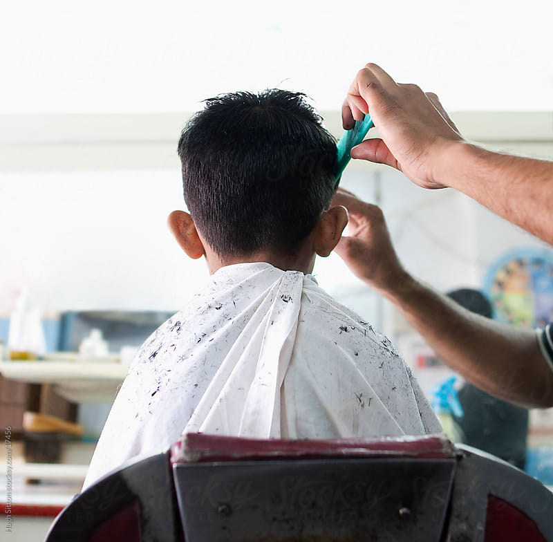 Young boy having haircut in barber shop by Hugh Sitton for Stocksy United