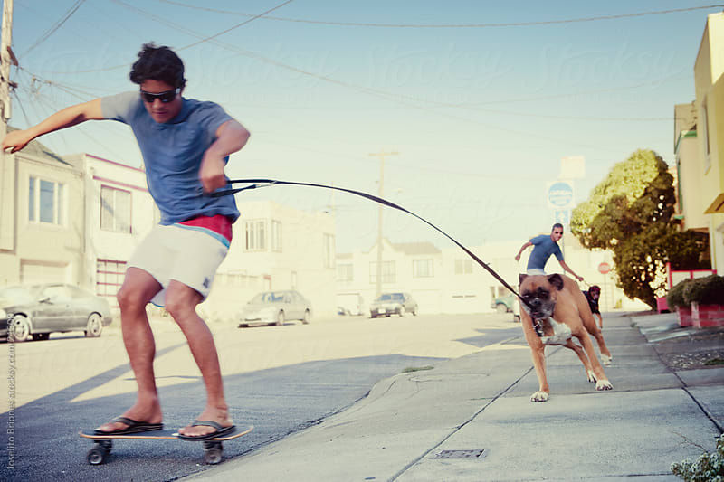 Men Running and Walking Dogs while Skateboarding by Joselito Briones for Stocksy United