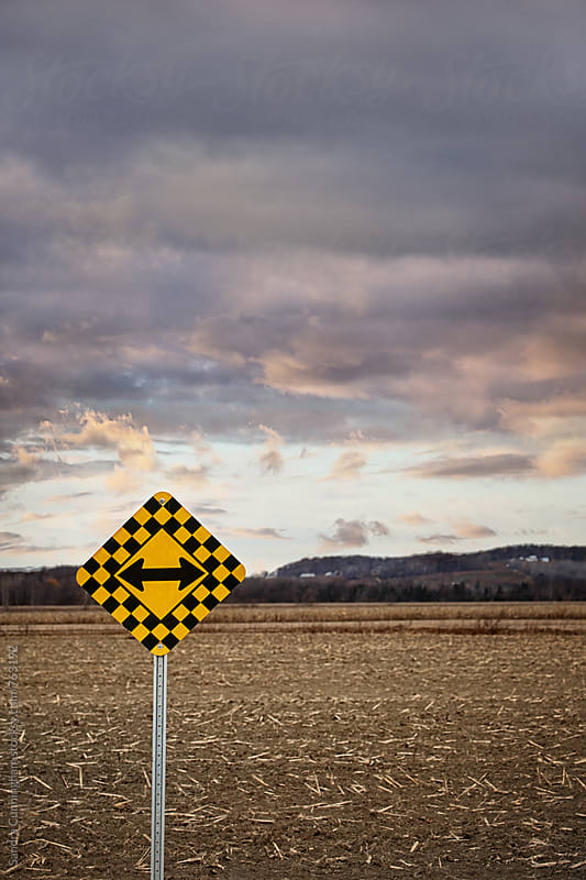 Country road with directional sign with dark clouds in background by Sandra Cunningham for Stocksy United
