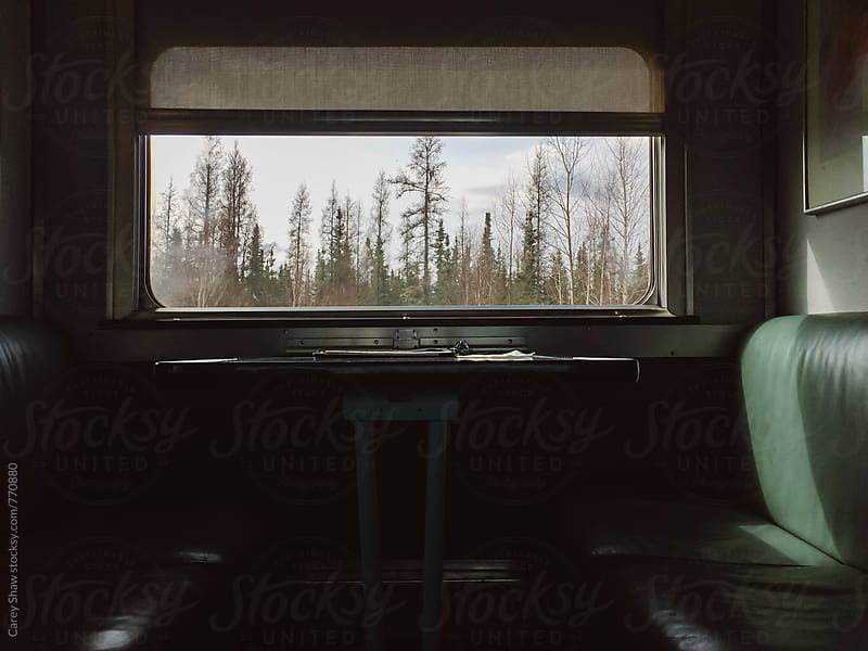 Picture window and table on train by Carey Shaw for Stocksy United