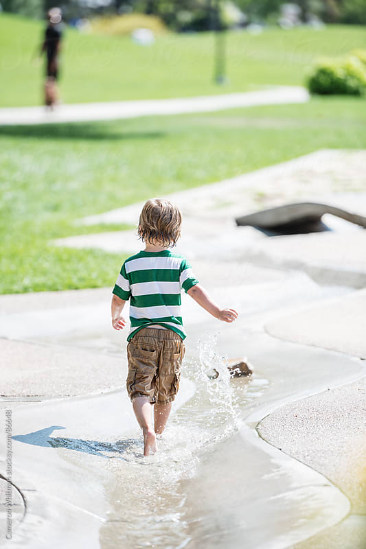 Boy running in playground waterway by Cameron Whitman for Stocksy United