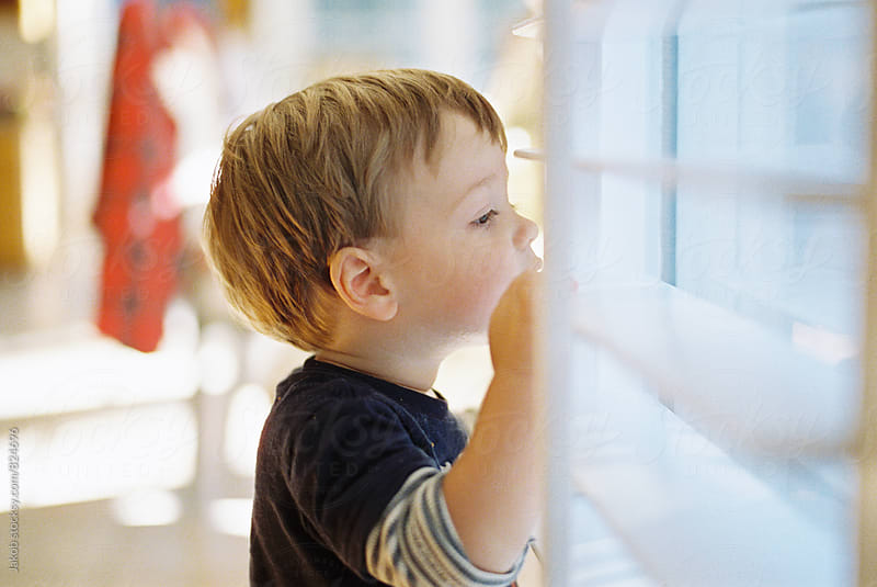 Cute young boy looking outside through blinds by Jakob for Stocksy United
