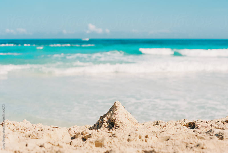 Small sand castle on Caribbean beach by Joey Pasco for Stocksy United