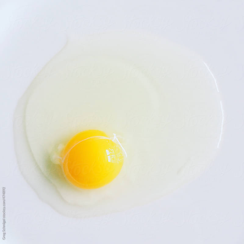 A single raw egg and yolk on a while table by Greg Schmigel for Stocksy United