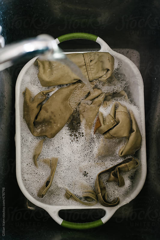 overhead view of dirty clothes soaking in a laundry tub by Gillian Vann for Stocksy United