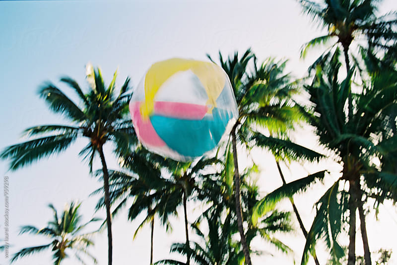 rainbow beach ball thrown in air in front of palm trees by wendy laurel for Stocksy United