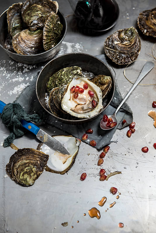 Oysters on metallic background with pomegranate and oyster knife opener by Marta Muñoz-Calero Calderon for Stocksy United